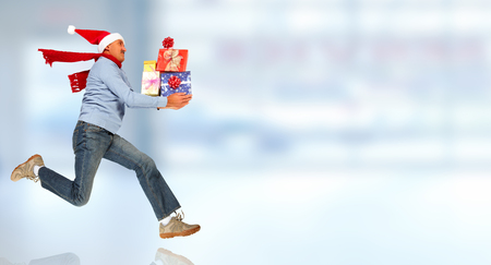 Happy man with Xmas gifts running over blue background. Banco de Imagens