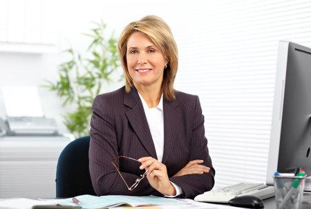 성숙한 비즈니스 여자 사무실에서 컴퓨터에서 작동합니다.