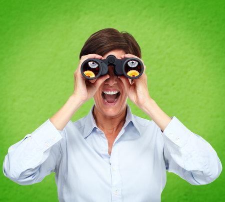 Mujer de negocios con los prismáticos sobre fondo verde.