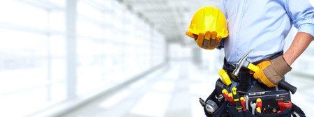 Złota rączka budowniczy z narzędzi budowlanych. Remont domu w tle.