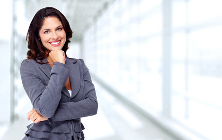 Beautiful young business woman over blue office background. Stockfoto