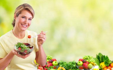 Ältere Frau, die Salat isst. Diät und Ernährung Konzept Hintergrund.