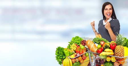 Happy young woman with grocery shopping cart over blue abstract background.