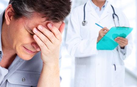 Hombre cansado con dolor de cabeza de migraña. El estrés y la salud.