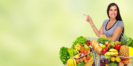 Gelukkige jonge vrouw met boodschappenwagentje op groene abstracte achtergrond.