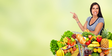 Happy young woman with grocery shopping cart over green abstract background. Stock Photo