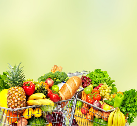 Grocery shopping cart with fruits and vegetables over green background.