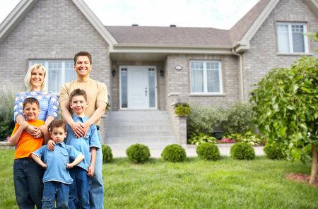 Glückliche Familie mit Kindern in der Nähe von neuen Haus. Bau und Immobilien-Konzept.