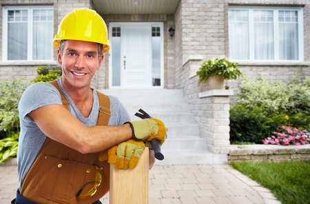 Handyman with wood and hammer. House renovation service.