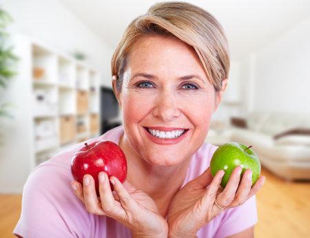 Senior lächelnde Frau mit Apfel. Ernährung und gesunde Gewichtskonzept.