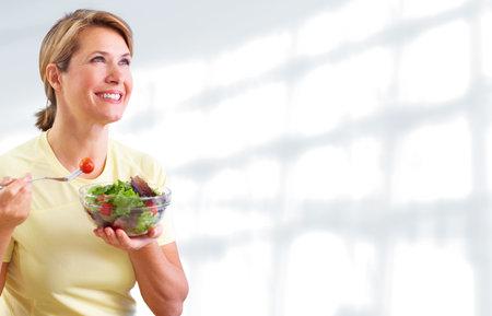 Ältere Frau, die Salat isst. Diät und Ernährung Konzept Hintergrund. Standard-Bild