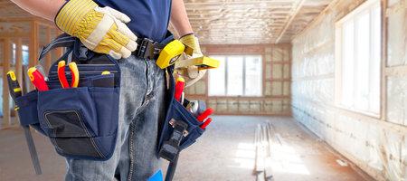 Costruttore tuttofare con strumenti di costruzione. Ristrutturazione casa sfondo. Archivio Fotografico