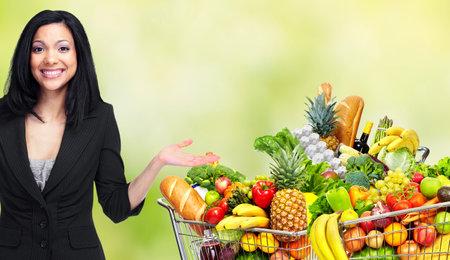 Mujer de Asia y el carrito de compras con las frutas y las verduras.