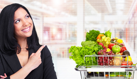 Asian woman and grocery shopping cart with fruits and vegetables.