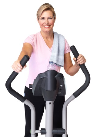 Mature beautiful woman doing exercise on elliptical trainer. Banque d'images