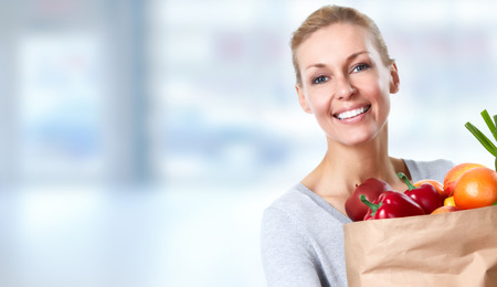 Bella donna che tiene la borsa della spesa con verdure su sfondo blu.