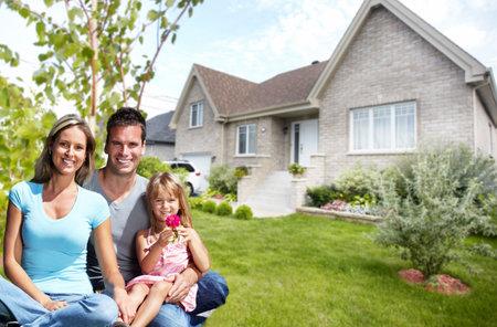 Gelukkige familie met kinderen in de buurt van het nieuwe huis. Bouw en onroerend goed concept.