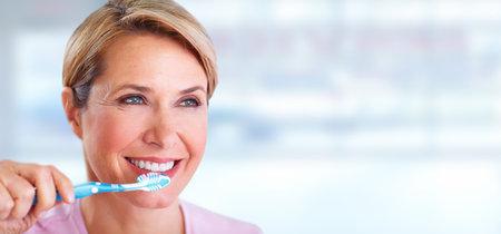 Bella donna sorridente senior con uno spazzolino da denti. l'assistenza sanitaria dentale.
