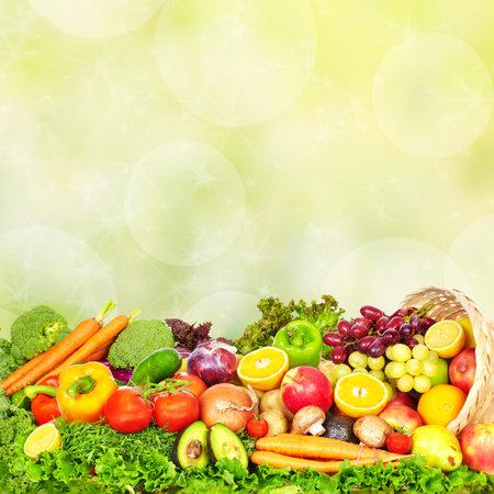 Frischgemüse und Früchte über grünem Hintergrund. Gesunde Ernährung.