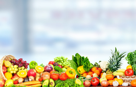 Fresh fruits and vegetables over green background. Stock Photo