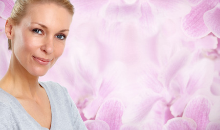 Beautiful woman face over floral background. Beauty and cosmetics. Banco de Imagens