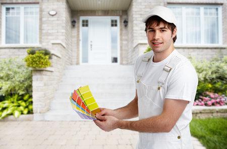 Pintor hombre cerca de la nueva casa. Renovación de la casa de fondo. Foto de archivo