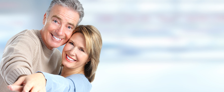 Happy senior couple in love over blue banner background.