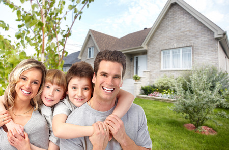 Happy family with children near new house. Construction and real estate concept.