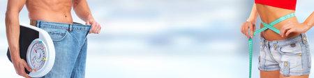 Afslanken man buik met grote broek over blauwe achtergrond. Stockfoto