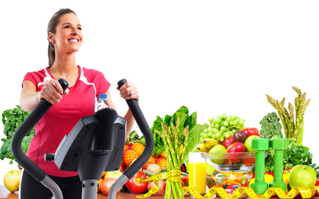 Beautiful woman exercising on elliptical trainer. Dieting and sport background.