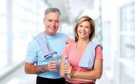 Senior uomo e donna con la bottiglia di acqua. Dieta e lo sfondo dello sport.