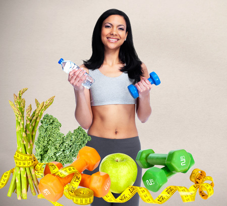 Healthy young woman with dumbbell. Dieting and sport background.