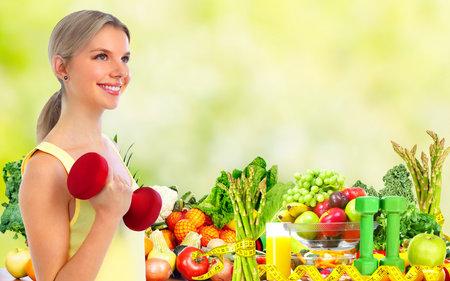 ダンベルを持つ健康な若い女性。ダイエットやスポーツの背景。