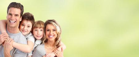 Familia feliz con los niños sobre fondo abstracto verde.