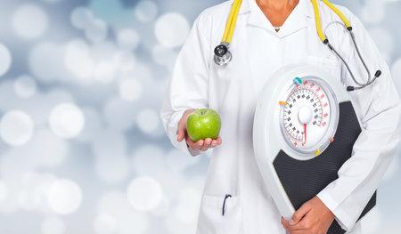 Arts vrouw handen met schalen en appel over gezondheidszorg achtergrond.
