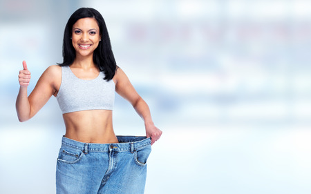 Slimming woman abdomen with big pants over blue background.