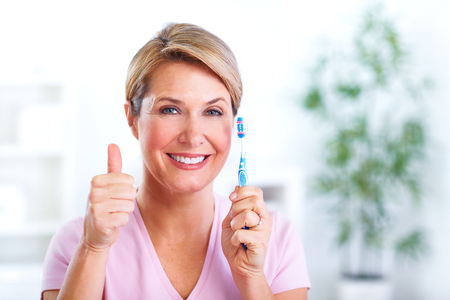 Beautiful senior smiling woman with a toothbrush. Dental health care.