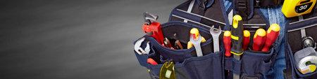 ceinture à outils avec des outils de construction sur fond gris.