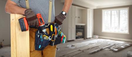 manitas del constructor con las herramientas de la construcción en el fondo de la casa. Foto de archivo