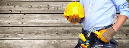 Builder handyman with construction tools on wooden background. Stockfoto