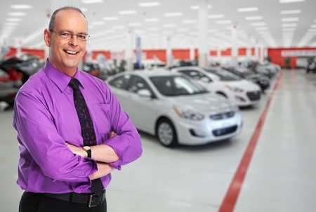 Car dealer man. Auto dealership and rental concept background. Stock Photo