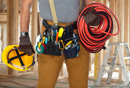Builder handyman with construction tools in new house background. Фото со стока