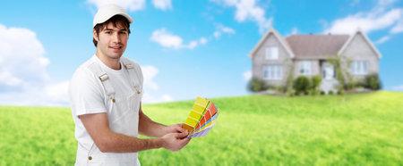 Maler Mann in der Nähe von neuen Haus. Hausrenovierung Hintergrund.
