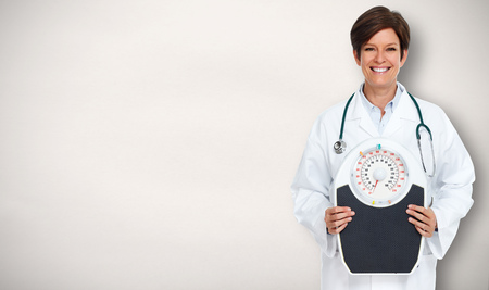 Mature medical doctor woman over gray background.