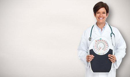 Rijpe vrouw van de arts over grijze achtergrond. Stockfoto