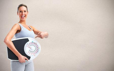 mujer sana con escalas sobre fondo gris.