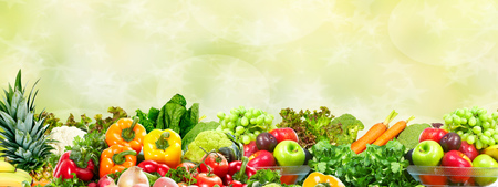 Fresh Vegetables and fruits over green background. Healthy diet. Banco de Imagens