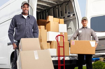 Lachend postbode met een doos in de buurt van de scheepvaart vrachtwagen. Stockfoto