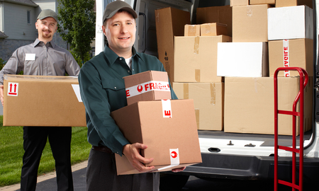 Smiling postman with a box near shipping truck.