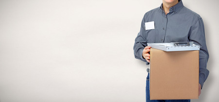 Delivery postman with a box over gray background. Stock Photo